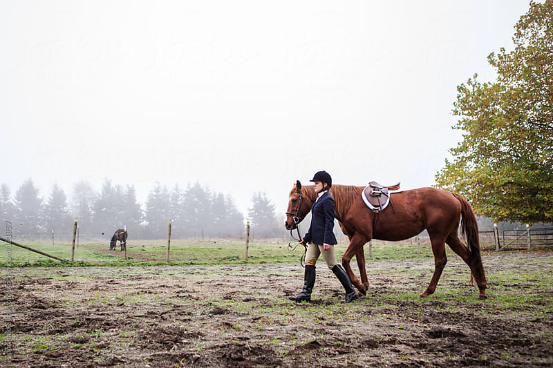 Woman walking her horse outside on the field by Suprijono Suharjoto for Stocksy United
