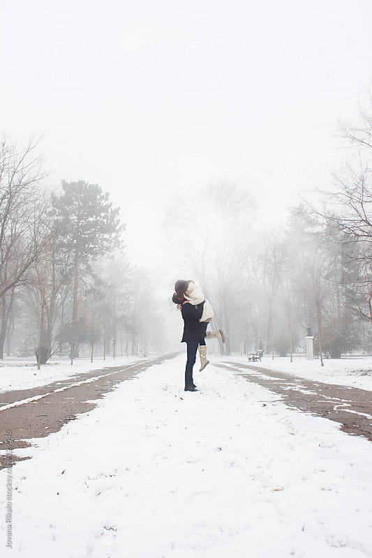 Young couple kissing in park while snowing by Jovana Rikalo for Stocksy United
