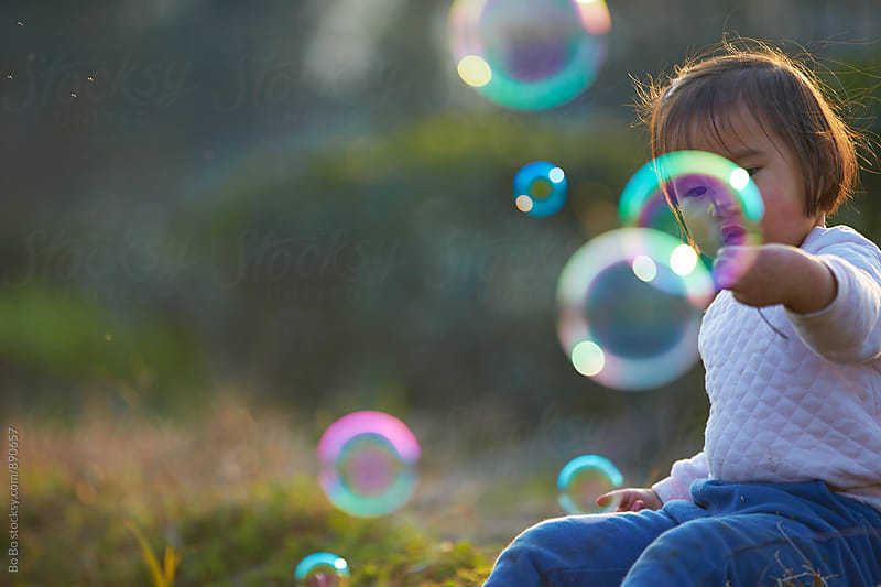 little asian girl playing with soap bubble by Bo Bo for Stocksy United