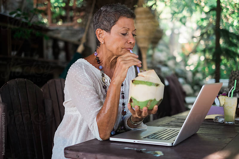 Senior Woman Drinking Coconut Milk and Working in a Tropical Cafe by Mosuno for Stocksy United