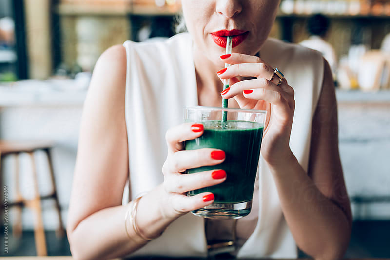Woman Drinking a Green Smoothie at a Cafe by Lumina for Stocksy United