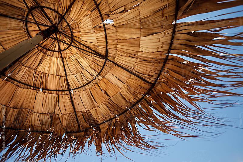 straw beach umbrella against a blue sky by Helen Sotiriadis for Stocksy United