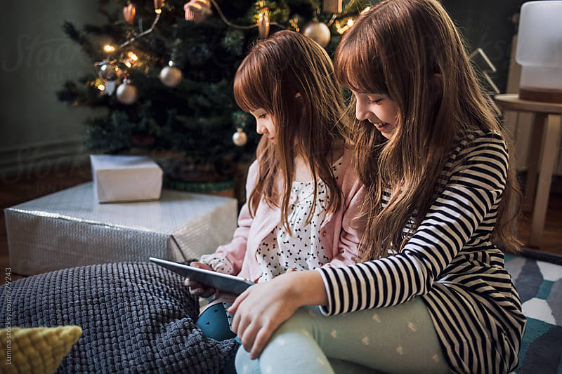 Sisters Playing on a Tablet at Christmastime by Lumina for Stocksy United