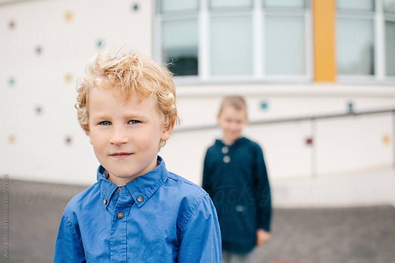 Two young boys in front of a school by Ania Boniecka for Stocksy United