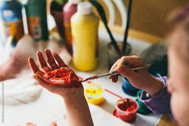 A child paints her hand with red paint. by Cherish Bryck for Stocksy United