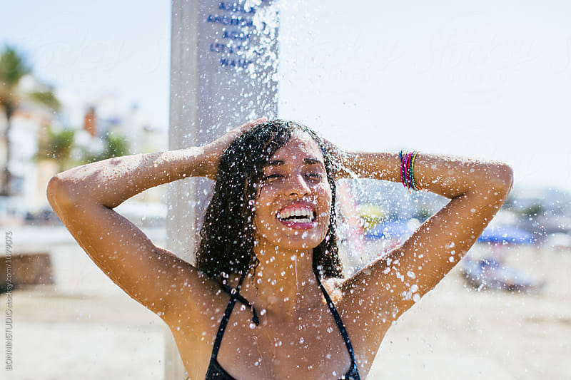Smiling woman taking a shower on the beach.  by BONNINSTUDIO for Stocksy United