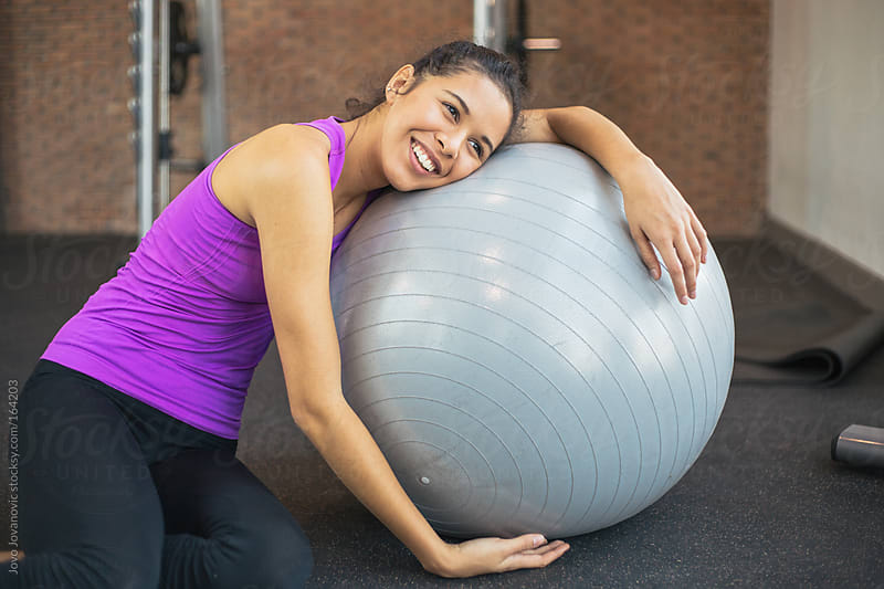 Fit young woman relaxing on a pilates ball by Jovo Jovanovic for Stocksy United