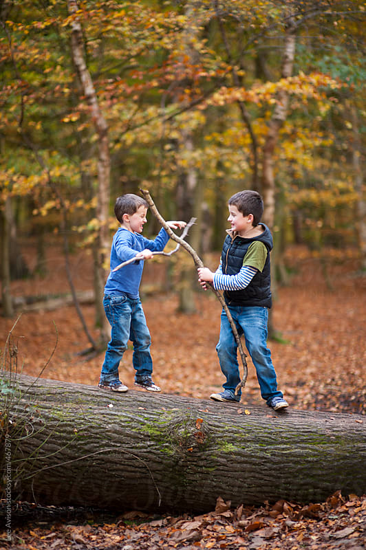 boys play fighting with sticks in a forest by Lee Avison for Stocksy United