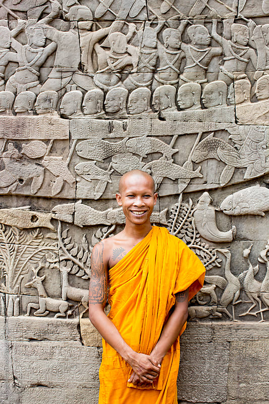 Buddhist monk standing in front of wall carvings. Bayon Temple. Angkor Wat. by Hugh Sitton for Stocksy United