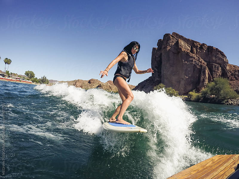 Woman Wakesurfing with Rock Cliff Background by MEGHAN PINSONNEAULT for Stocksy United