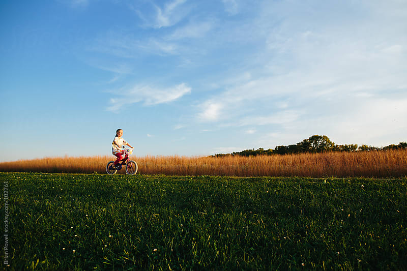 girl riding bike across landscape by Brian Powell for Stocksy United