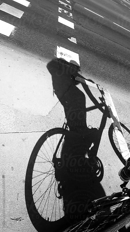 bicyclist shadow in the street in black and white by Sonja Lekovic for Stocksy United