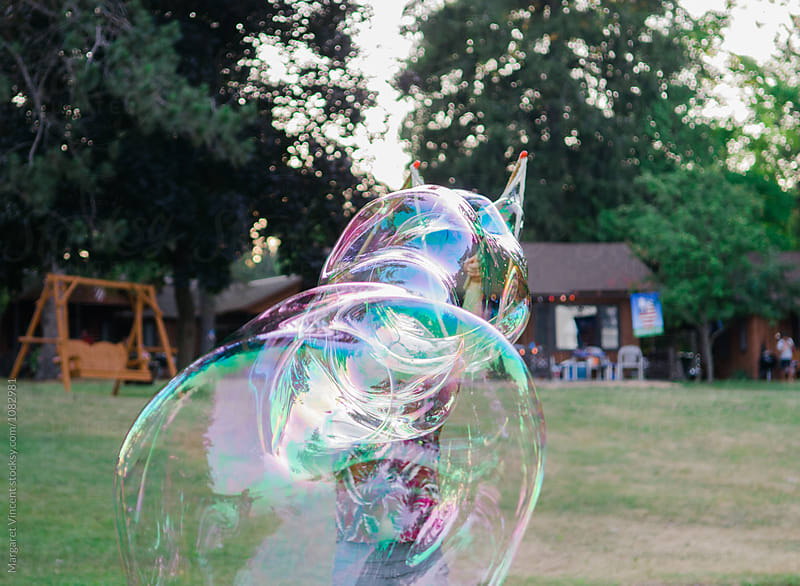man obscured by huge bubbles by Margaret Vincent for Stocksy United