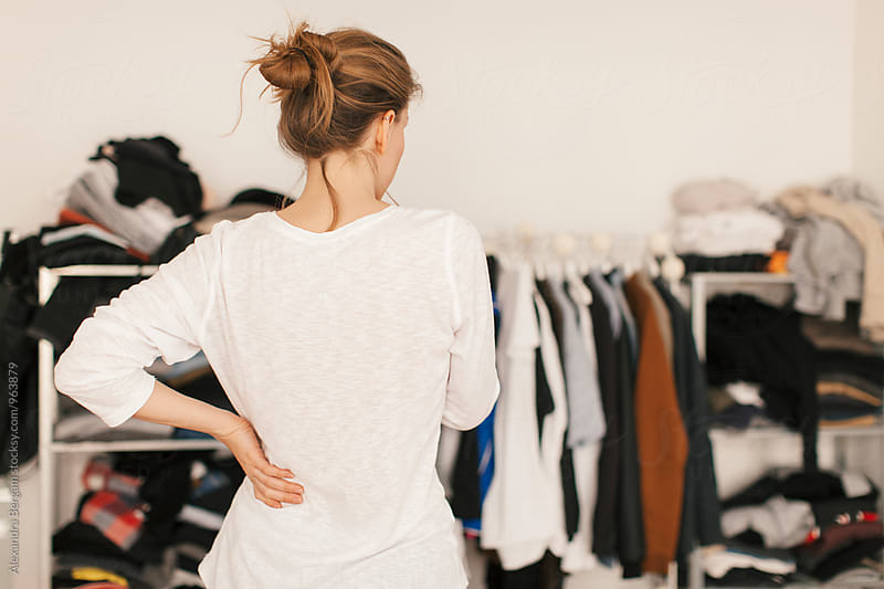 woman in front of the wardrobe thinking what to wear by Aleksandra Kovac for Stocksy United
