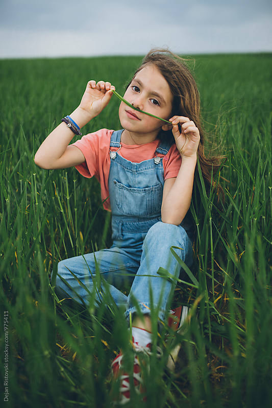 Portrait of cute calm girl with blade of grass near nose by Dejan Ristovski for Stocksy United