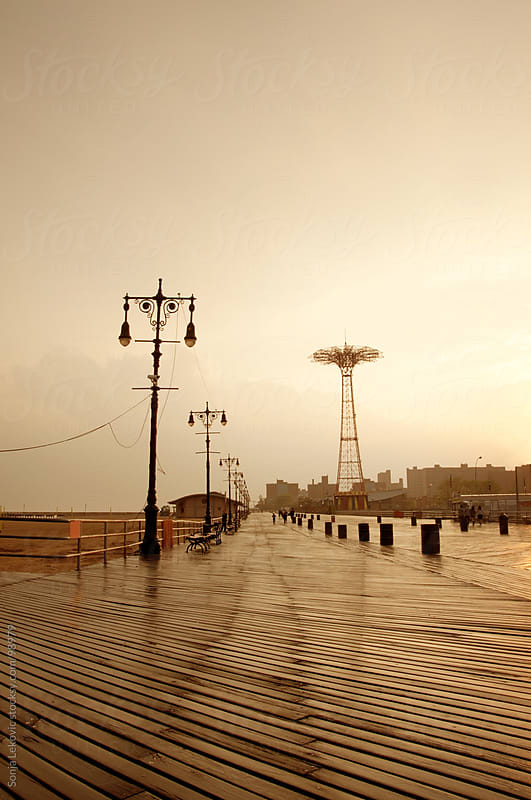 sunset on coney island boardwalk in new york city by Sonja Lekovic for Stocksy United
