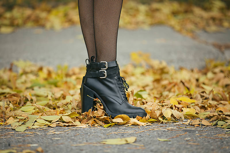 Black boots  in a pile of yellow leaves by Ania Boniecka for Stocksy United