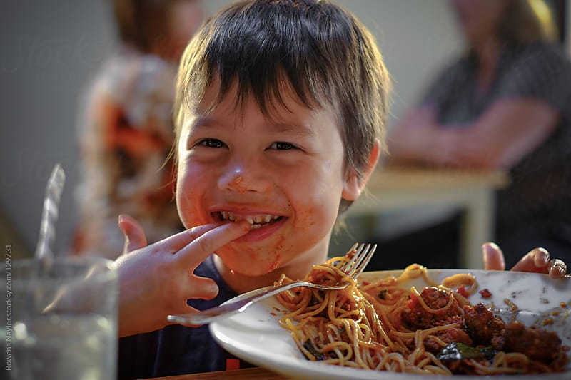 Kid eating spaghetti bolognese by Rowena Naylor for Stocksy United