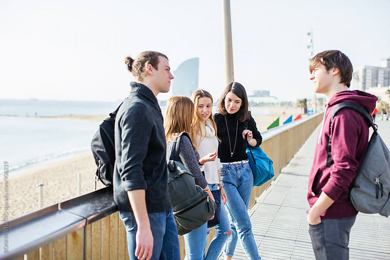Group of teen students talking after school on the street. by BONNINSTUDIO for Stocksy United
