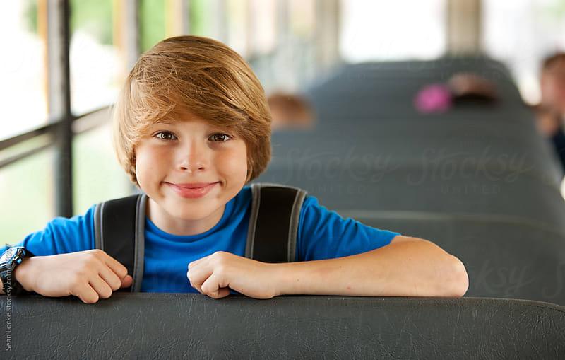 School Bus: Kid Leans over Bus Seat by Sean Locke for Stocksy United