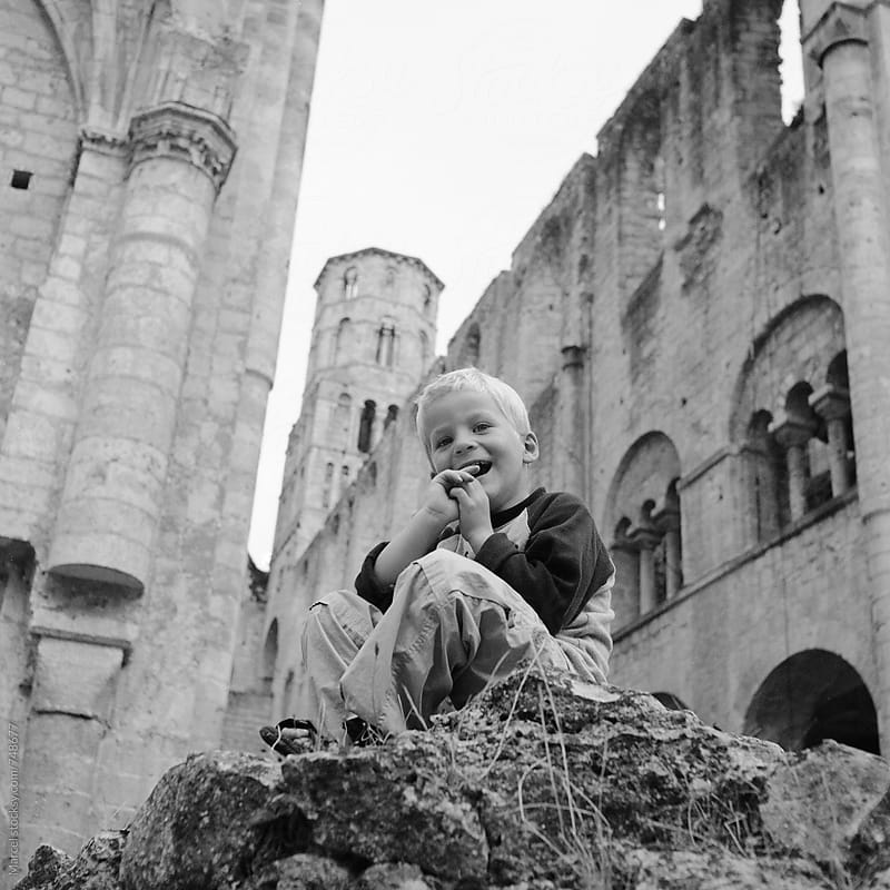 Laughing boy on ruins of a cathedral by Marcel for Stocksy United