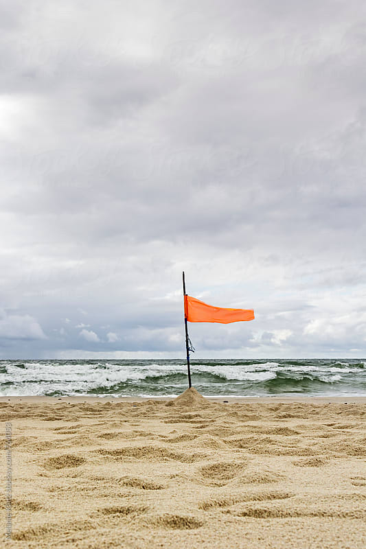 Orange flag at the beach at the sea by Melanie Kintz for Stocksy United