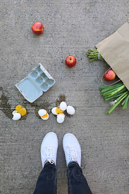 Person standing above spilled groceries and broken eggs by Carolyn Lagattuta for Stocksy United