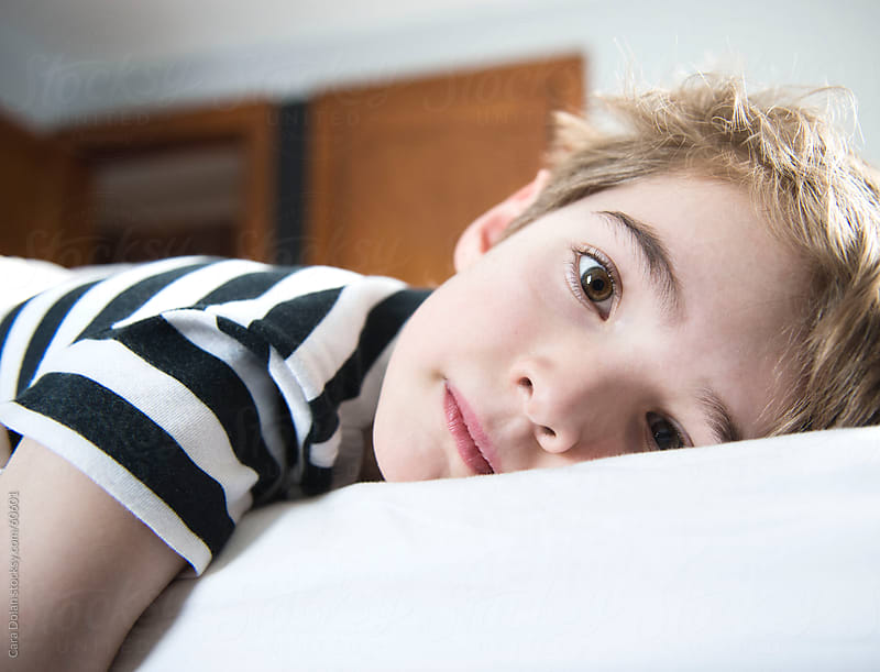 Boy lying on bed looks directly at camera by Cara Slifka for Stocksy United