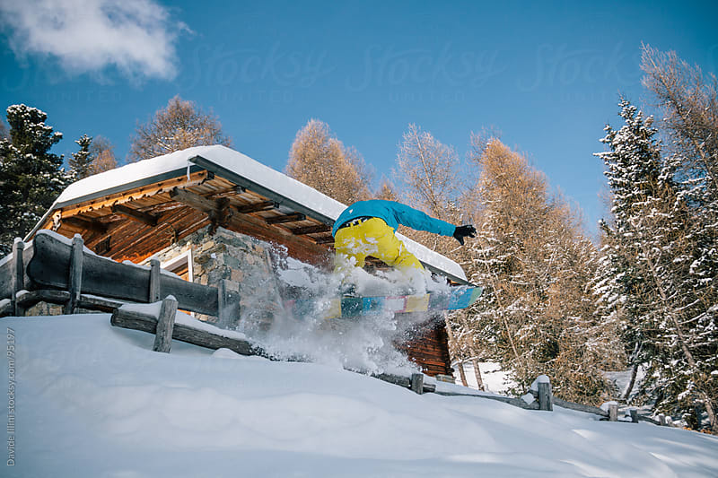 Snowboarder jumping in powder snow by Davide Illini for Stocksy United