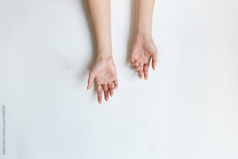 Hand holding jewelry on white by Sophia Hsin for Stocksy United
