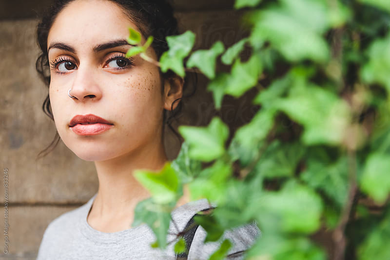Beautiful Mixed Race Girl Hidden Behind Plants by Giorgio Magini for Stocksy United