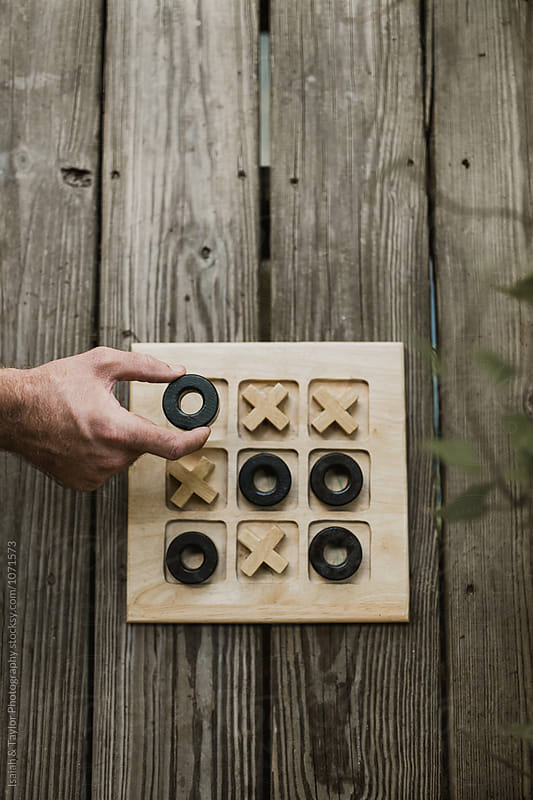Hand playing Tic Tac Toe by Isaiah & Taylor Photography for Stocksy United