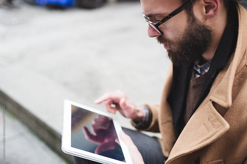 Young man using his digital tablet outdoors by michela ravasio for Stocksy United