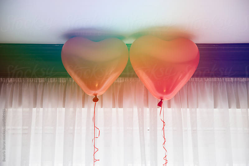 Double exposure of two red heart balloons exposed on rainbow light reflection by Beatrix Boros for Stocksy United