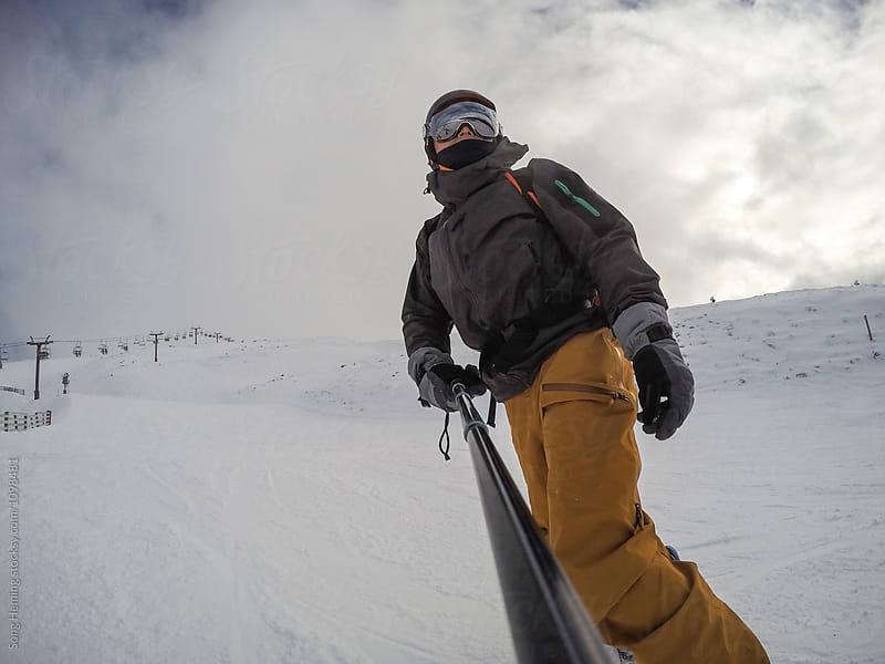 A snowboarder taking selfie photo at ski area