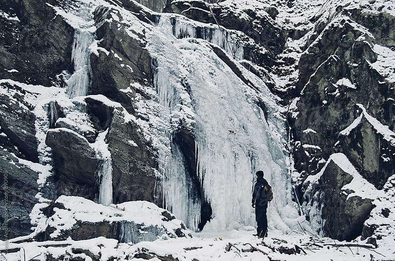 Man near frozen waterfall in cold winter by Cosma Andrei for Stocksy United