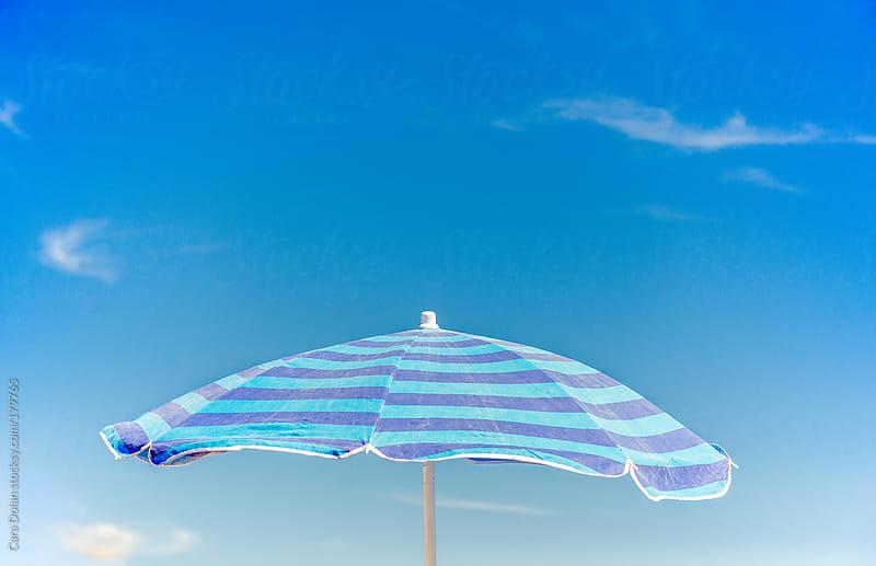 Blue striped beach umbrella against blue sky by Cara Dolan for Stocksy United