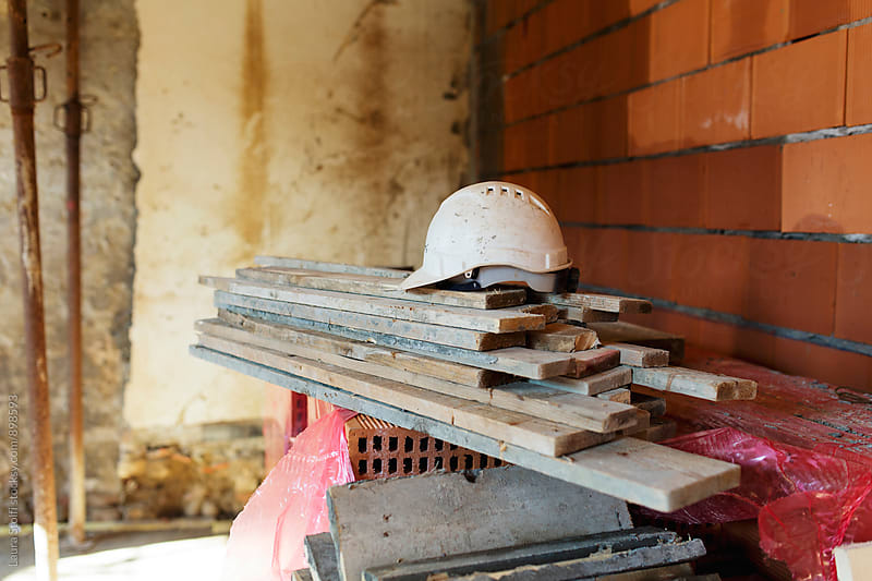 Safety helmet on top of wooden boards on building site by Laura Stolfi for Stocksy United