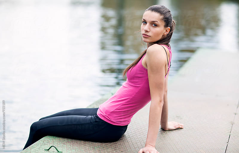 Woman resting on the dock after training by MEM Studio for Stocksy United