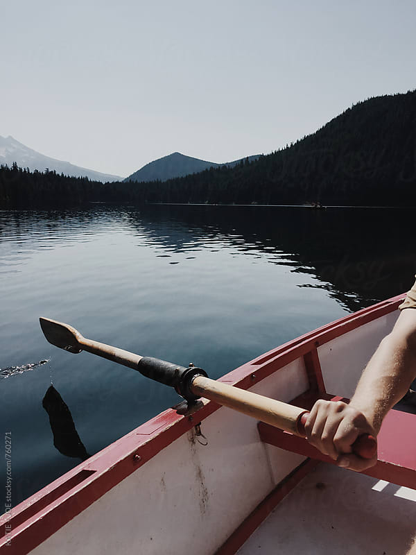 Row boat on a lake with a mountain view by KATIE + JOE for Stocksy United