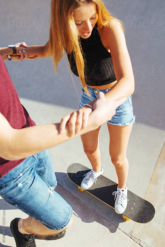 Teenage couple having fun in a skate park in summer.  by BONNINSTUDIO for Stocksy United