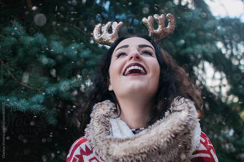 A woman wearing reindeer ears looking up at the snow by Chelsea Victoria for Stocksy United