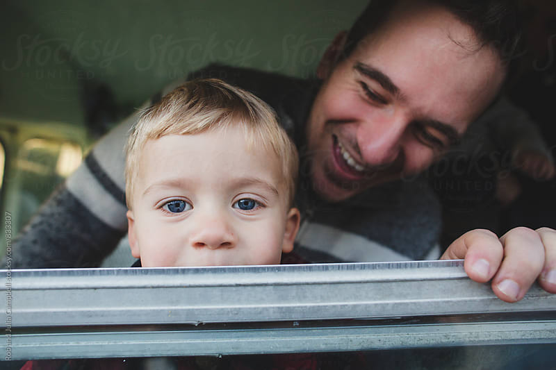 Toddler boy looking out window with laughing dad behind by Rob and Julia Campbell for Stocksy United