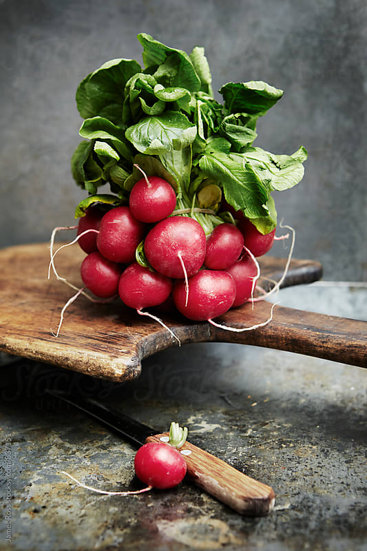 Radish with leaves on a wooden board by James Ross for Stocksy United