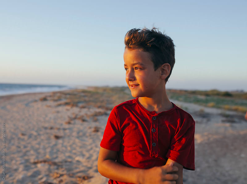 Boy looking at sunset. by Dejan Ristovski for Stocksy United