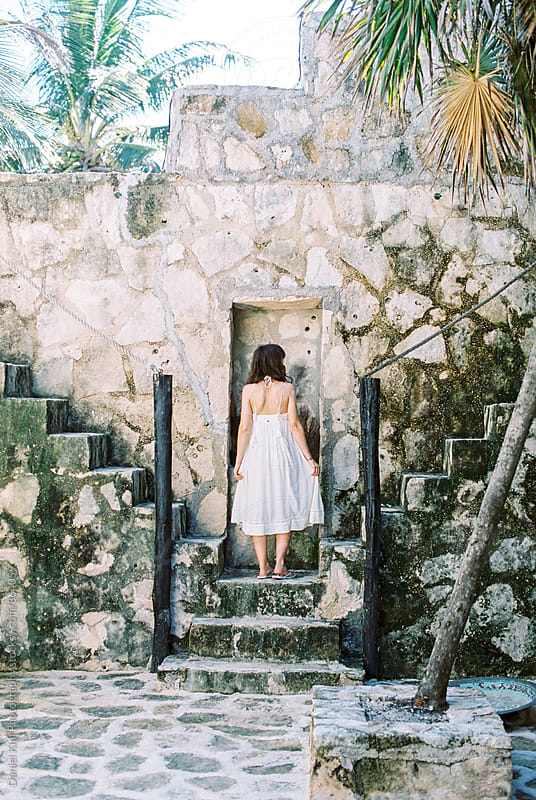 Woman walking up stone steps by Daniel Kim Photography for Stocksy United
