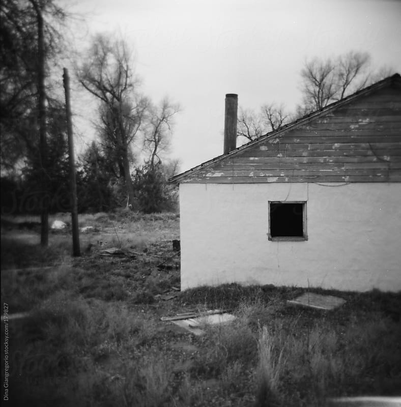 deserted old house in country in black & white film by Dina Giangregorio for Stocksy United