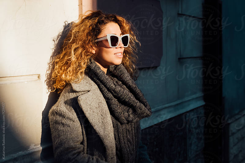 Portrait of Beautiful Young Woman With Curly Hair And Sunglasses by Katarina Radovic for Stocksy United