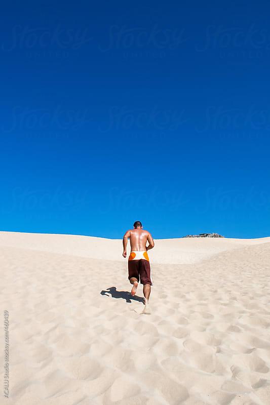 Man running on dune in Cadiz beach by ACALU Studio for Stocksy United