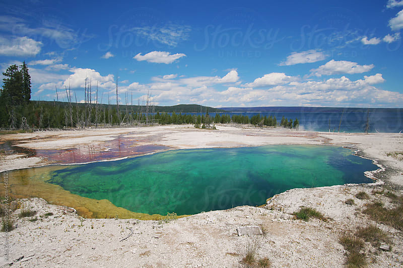 A beautiful deep, turquoise colored hot spring in Yellowstone National park. Yellowstone lake can be seen in the background. by Kaat Zoetekouw for Stocksy United